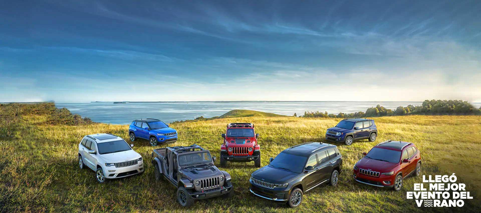 """La línea Jeep 2021 en una colina verde que mira hacia el agua. Adelante: un Jeep Grand Cherokee Summit, Gladiator Rubicon, Grand Cherokee L y Cherokee Limited. Atrás: unCompass Limited, Wrangler Rubicon4xe y Renegade Limited. El logo """"Conviértelo en el evento del verano"""""""